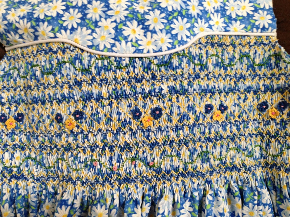 Close up of blue daisy dress smocking.